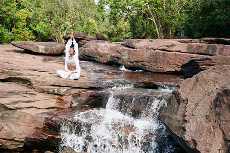 Beautiful young woman sitting by waterfall and enjoying meditation in nature 版權商用圖片
