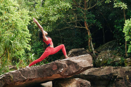 Slim young woman standing on rock in tropical forest and doing warrior pose