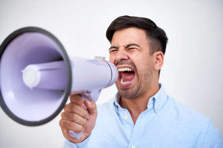 Young man closing eyes when screaming out loud in megaphone at business meeting or political gathering
