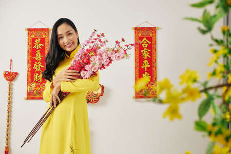 Portrait of attractive young Asian woman holding blooming peach branches she bought to decorate apartment for Chinese New Year
