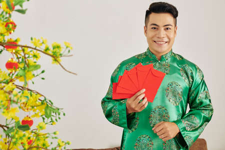 Portrait of young attractive Asian man holding red envelopes for Tet celebration