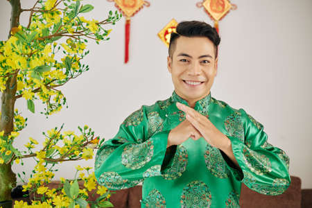 Happy smiling Vietnamese young man in traditional costume making special gesture to wish happy Lunar New Year