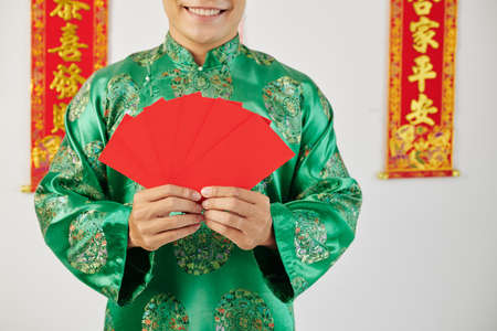 Cropped image of happy Asian man holding many red envelopes for Lunar New Year celebration