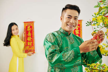 Handsome young man hanging fire crakers on blooming apricot tree when his girlfriend hanging scroll with best wishes inscription on wall in background