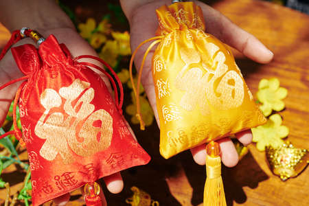 Red and golden textile bags with best wishes embroidery as gifts for spring festival