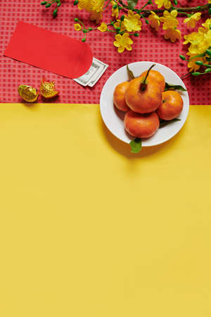 Chinese New Year background with plate of tangerines and lucky money envelopes