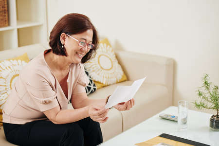 Happy middle-aged Asian woman looking at old photos and remembering good old times