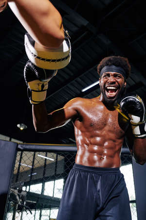 Professional male boxer with defined body sparring with his unrecognizable trainer on ring in gym vertical portrait
