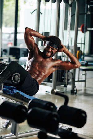 Vertical shot of African American guy working hard on his abs on abdominal bench in gym