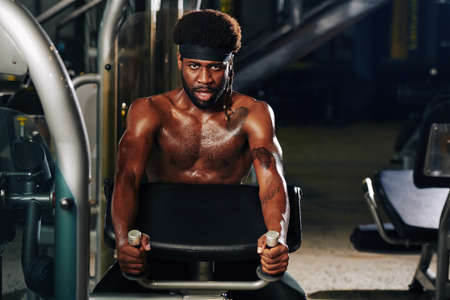 Horizontal portrait of serious sportsman doing strengthening exercise in gym looking at camera