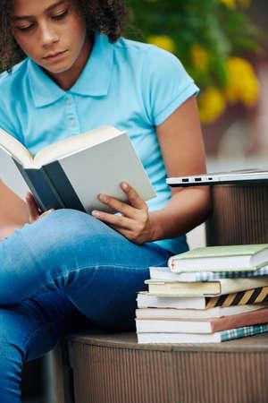Gilr assis sur un banc à l'extérieur et lisant un livre