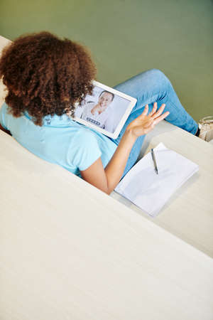 Vertical high angle shot of teen girl watching online lesson and having problems with understanding something 版權商用圖片