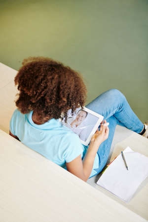 Vertical high angle shot of unrecognizable girl having privite distance learning online lesson on her pad