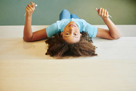 Horizontal top view shot of pozitive girl of mixed race relaxing in modern library room looking at camera