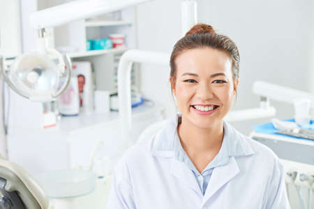 Horizontal head and shoulders shot of attractive young woman wearing white coat sitting in dentist's office looking at camera smiling