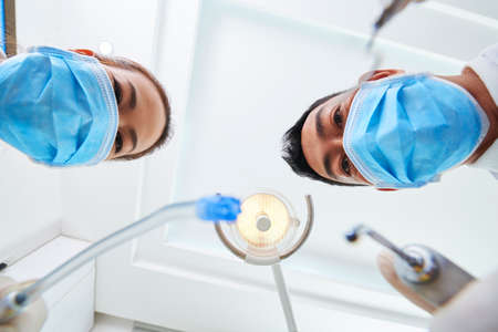 Horizontal point of view shot of two Asian dentists wearing protective masks starting dental surgery