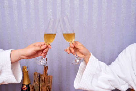 Unrecognizable couple wearing white robes clinking glasses with sparkling wine, horizontal shot