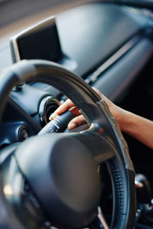 Close-up image of female driver adjusting speed of windshield wipers