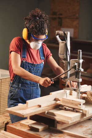 Young female carpenter in protective eyewear and ear defenders pressing lever on woodworking machine while cutting wooden planks