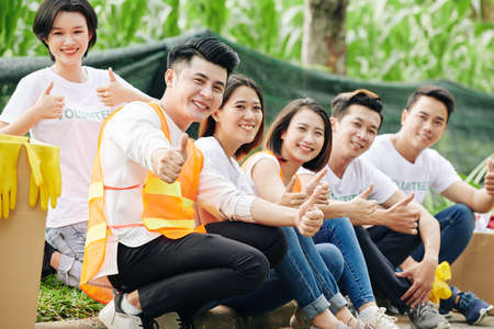 Happy young Asian students volunteers sitting outdoors, smiling and showing thumbs-up