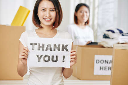 Lovely pretty young Asian woman with thank you placard in hands working at donation center