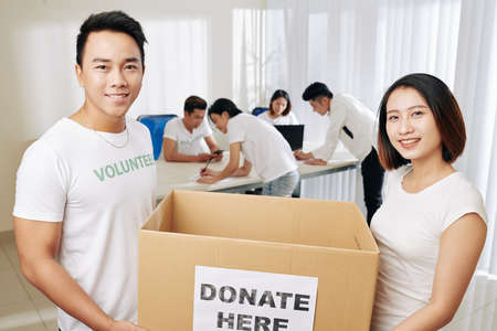 Happy Asian young people carrying big box for donation of clothes and food for people in need