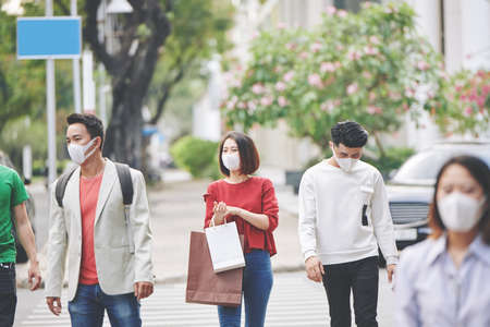 Asian people walking in city street with protective masks on to protect themselves from polluted air Standard-Bild