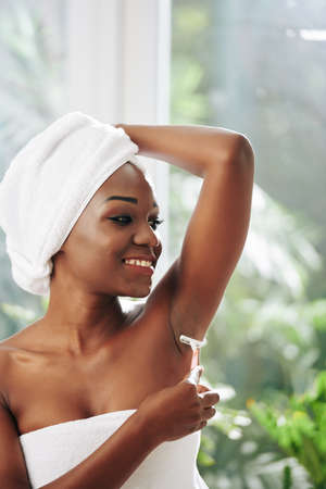 Vertical portrait of attractive young Black woman shaving her armpits in weekend morning looking away
