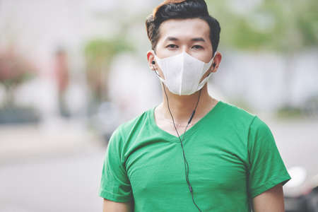 Serious young Asian man lisening to music in headphones when walking outdoors in protective mask during coronavirus outbreak period