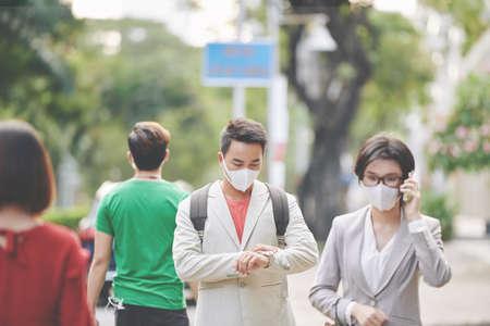 Asian people in medical masks protecting against viruses and diseases crossing road