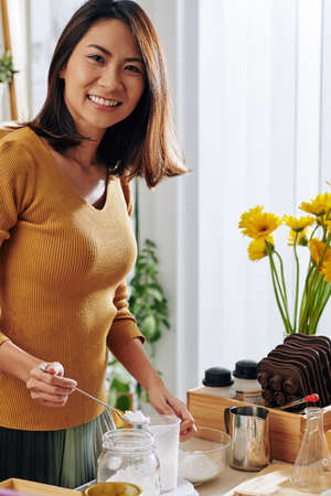 Happy young Vietnamese woman adding dry ingredients into glass bowl when making soap at home