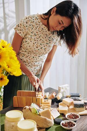 Giovane donna creativa che usa un coltello speciale per tagliare il sapone fatto a mano in piccole barre Archivio Fotografico
