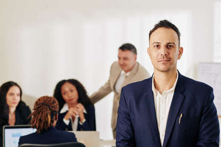 Portrait of smiling handsome businessman looking at camera when his coworker working on new creative project in background Reklamní fotografie