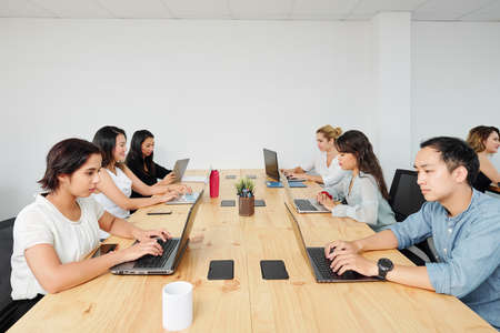 Young software developers working on laptops at big wooden office table Stock Photo