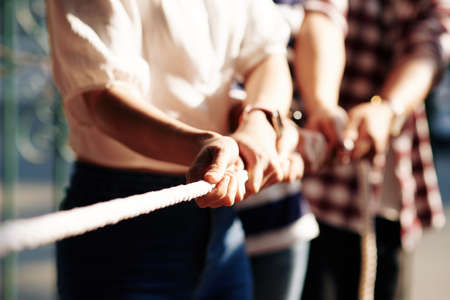 Cropped image of coworkers playing tug of war for developing cooperation and support in business team Imagens