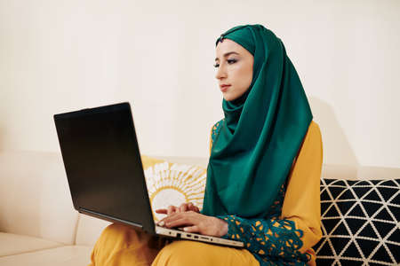Muslim female freelance programmer sitting on sofa at home and working on laptop