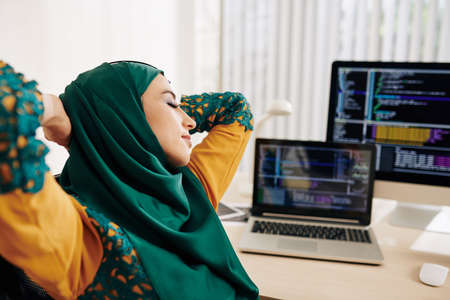 Young muslim woman stretching in her chair after working on programming code Stock Photo