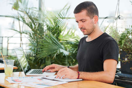 UX designer checking printed documents in front of him when working on laptop at cafe table Stock Photo