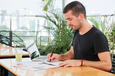 Freelance UI designer checking printed documents with new mobile app interface and taking notes in planner
