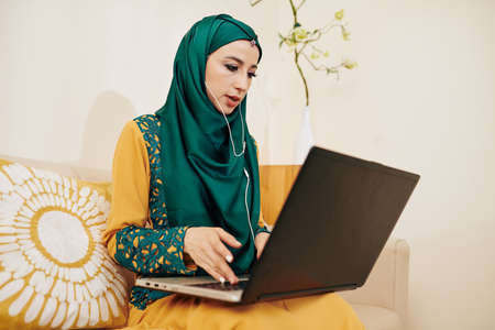 Muslim female entrepreneur wearing earbuds when making video call to business partner or client to discuss project Stock Photo
