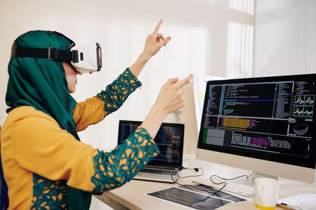 Muslim young woman sitting at her office desk and testing virtual reality application she created