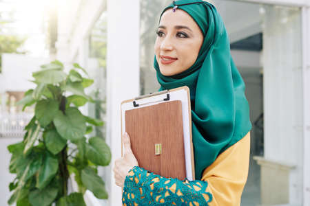 Portrait of young pretty muslim businesswoman standing outdoors with clipboard and folder