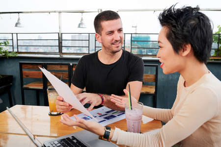 Positive young ux designer discussing his new creative ideas with client when meeting in cafe Stock Photo