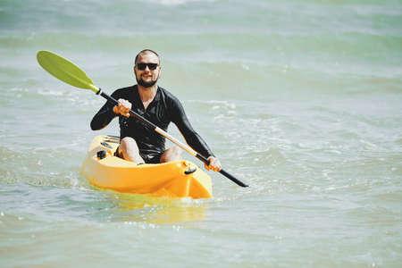 Handsome smiling young man in sunglasses enjoying kayaking in warm sea on weekend Banco de Imagens
