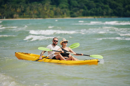 Happy young couple spending weekend together and paddling kayak on lake