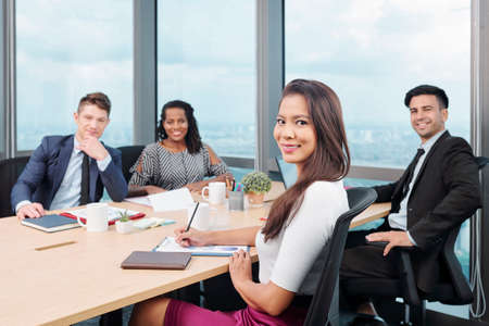 Smiling young Asian businesswoman attending meeting with colleagues where they discuss charts and reports Stock Photo