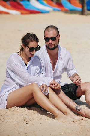Positive young couple in sunglasses and white shirts enjoying resting on beach after swimming