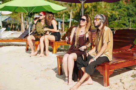 Positive couples sitting on wooden chaise-lounges on the beach, drinking beer and enjoying beautiful view Banco de Imagens
