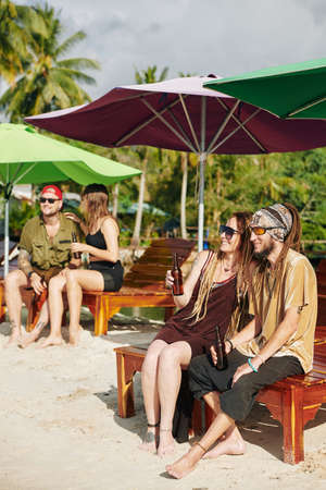 Group of smiling young people resting on beach and drinking tasty cold beer
