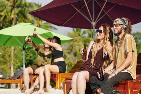 Positive people sitting on chaise-lounge on beach, drinking beer and enjoying sunny day